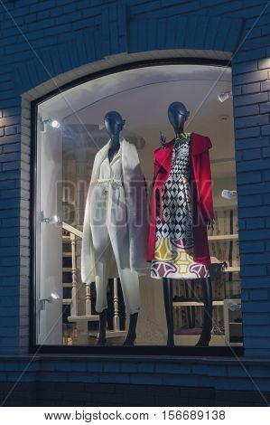 Female mannequins in fashionable dress on storefront