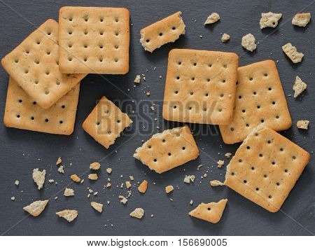 Square crackers with pieces and crumbs on slate gray background. Dry salt cracker cookies with fiber and dry spices. Top view or flat lay.