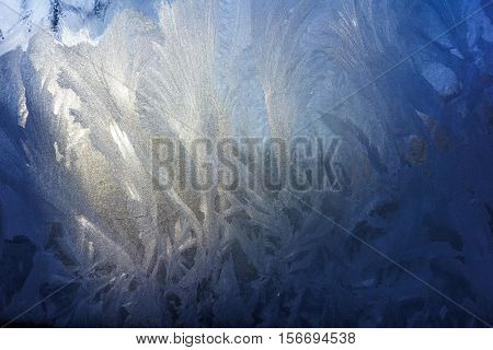 Blue Frost Background, Beautiful Closeup Winter Window Pane Coated Shiny Icy Frost Patterns, Low Temperature, Natural Ice Pattern on a Frosty Glass