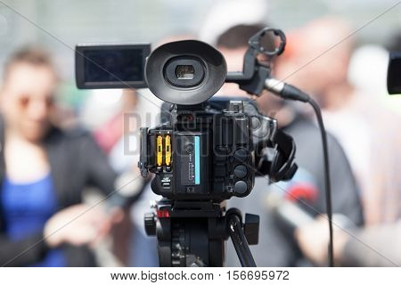 Filming an event with a video camera. TV broadcasting. News conference.
