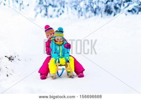 Boy and girl enjoying sleigh ride. Child sledding. Toddler kid riding a sledge. Children play outdoors in snow. Kids sled in the Alps mountains in winter. Outdoor fun for family Christmas vacation.