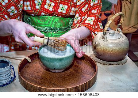 Tools used for Japanese tea ceremony (chado). A brush made of bamboo and a teacup with green tea called matcha on wooden tray. And tea master in kimono.