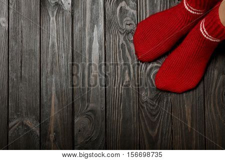 Legs knitted red wool socks on wooden dark background.