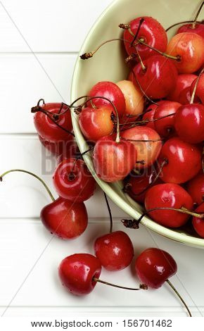 Heap of Fresh Ripe Sweet Maraschino Cherries in Green Bowl Cross Section on Plank White background. Top View