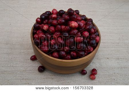 Fresh red and maroon cranberries heaped in turned wooden bowl with several berries outside the dish. Photographed close up against a woven ecru fabric with shallow depth of field and fill flash.