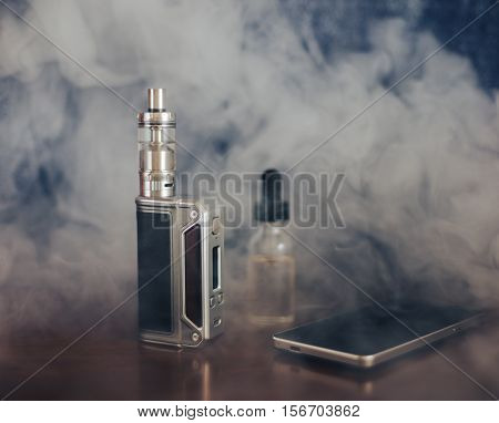 Vape devices, E-cigarette for vaping, liquid in the bottle and mobile phone at smoke on wooden table