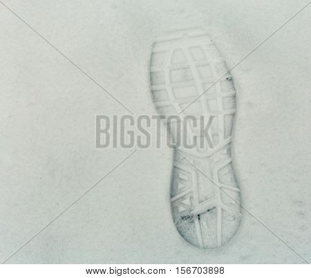 Trail of snowshoes on a snowy road. Boot trace on snow background