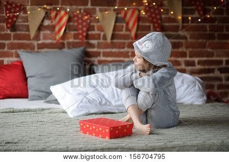 Little girl in a pajamas sits alone on a big bed. Before her a bright box with a gift. The child isn't happy. Girl is disappointed with a gift. She doesn't want to look at this gift. Offense. Protest.
