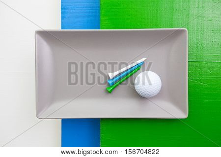 Gray ceramic dish with golf equipments on over white blue and green wooden table rectangle dish