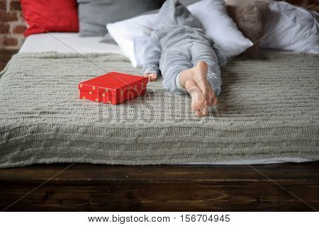 The child in pajamas lies on the big bed with his face buried in the pillow. Nearby there is a bright red box with a gift. The child isn't happy. He is disappointed with a gift and doesn't want to look at this gift. Offense. Protest.
