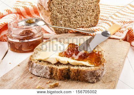 slice traditional irish sodabread with margarine and orange marmalade on a wooden board with knife