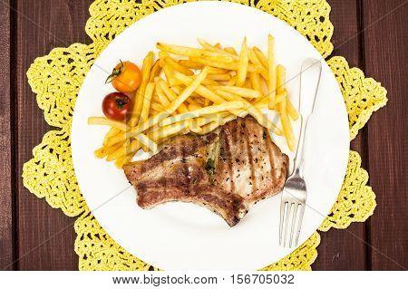 Loin Roast with Potatoes Fries on White Plate Studio Photo
