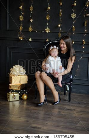 Cute woman with little daughter on hands sits in a beautiful chair. Room is festively decorated. On floor boxes with gifts lie. Ruddy baby in white dress with a wreath on head is similar to an angel.