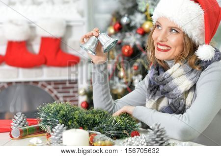 Portrait of young beautiful woman in Santa hat holding christmas decoration, silver bells
