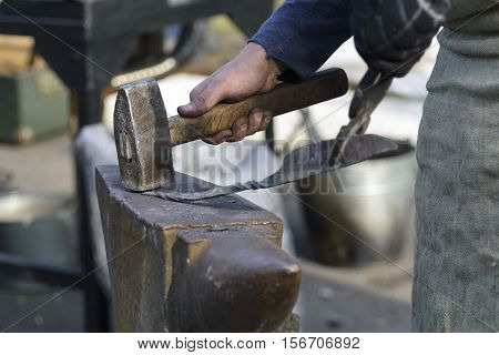 blacksmith forges detail. Blacksmith working outdoors. Master works on the anvil. Blacksmith makes a knife. poster