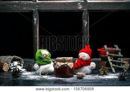 Handmade toy snowman and snowgirl of yarn skeins packing raspberry jam over black background. Color toning