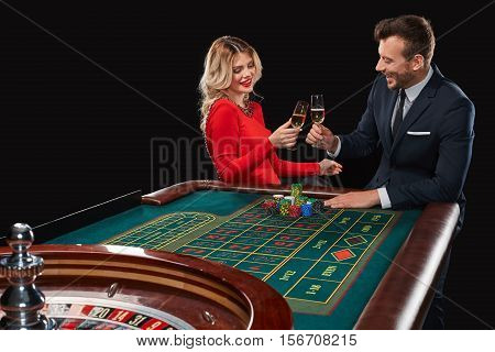 Couple playing roulette wins at the casino. Addiction to the gambling. celebrating the victory and win