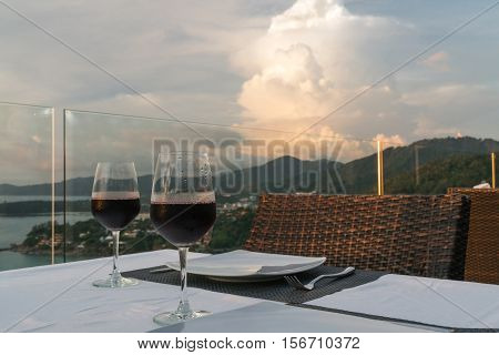 Two glasses of red wine on a background of sunset skyscape.