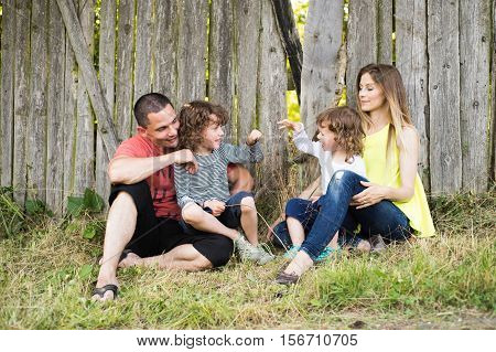 Beautiful young mother and father with their two little sons playing games called rock paper scissors, sitting against old wooden fence. Green sunny summer nature.