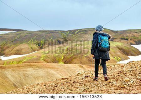 female hiker on the trail in the Islandic mountains. Trek in National Park Landmannalaugar, Iceland