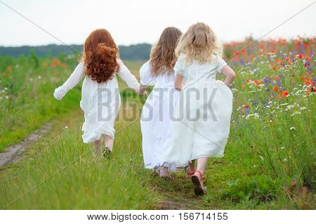 three young people running in the field