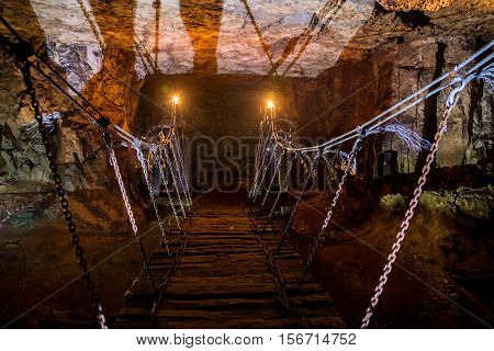 Old wooden bridge illuminated by candles in an abandoned limestone mine in Sock, Samara region