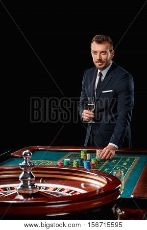 man in a suit playing roulette. addiction to gambling. In the hands of a glass. He bets chips