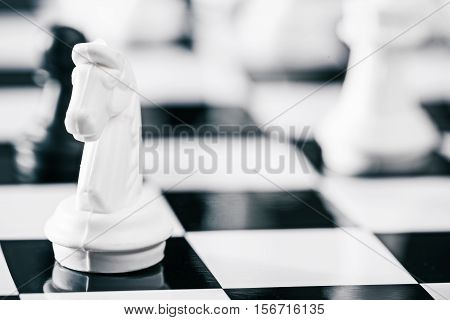 Moment of a chess game. White horse on the foreground. Macro view