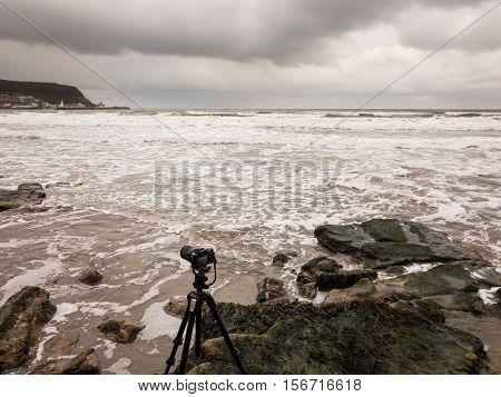 SCARBOROUGH ENGLAND - NOVEMBER 6: Camera on tripod ready to take photos of stormy seas. In Scarborough England. On 6th November 2016.