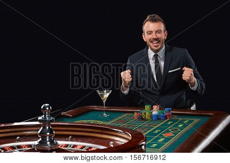 man in a suit playing roulette. addiction to gambling. In the hands of a glass. rejoices win
