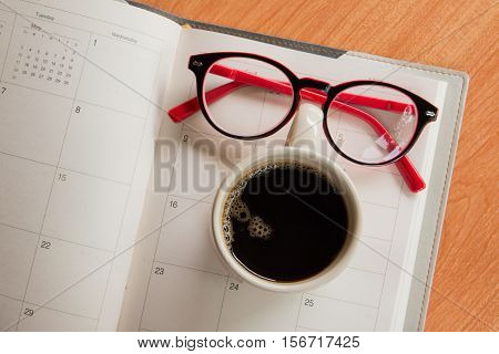 Cup of coffee and glasses on notebook with calendar planner on wooden desk background, top view