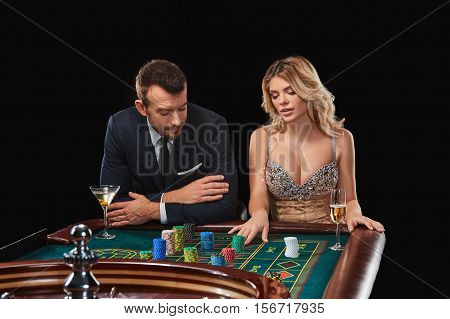 Couple playing roulette wins at the casino. Addiction to the gambling. Girl bets chips