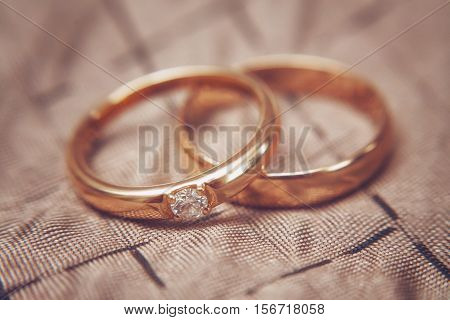 Two beautiful wedding rings with brilliants close up, vintage toned