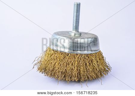 Round brass brush to be mounted on drilling machine over white background