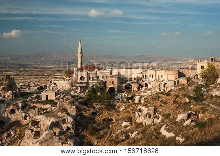 Minaret in Uchisar and the ruins of cave settlements. Cappadocia Turkey.