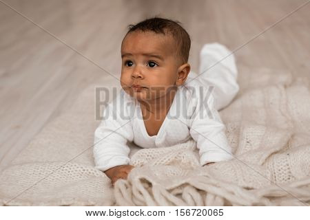 Thoughtful biracial mix of Hispanic and African American infant lying down on yellowish colored blanket