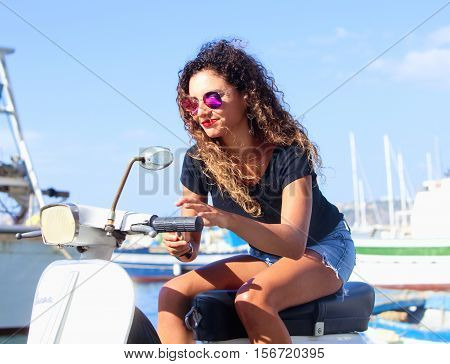 Young Italian Woman with Long Curly Hair on Vespa