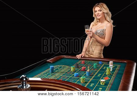 woman in a smart dress plays roulette. addiction to gambling. holding hands in a glass