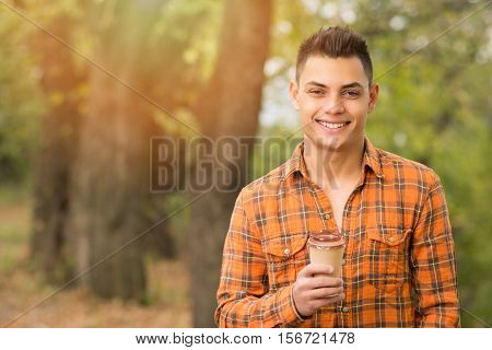 Cheerful young mixed race brunet man, with cup of takeaway coffee in park in autumn. Vibrant colors, closeup, copy space, medium retouch.