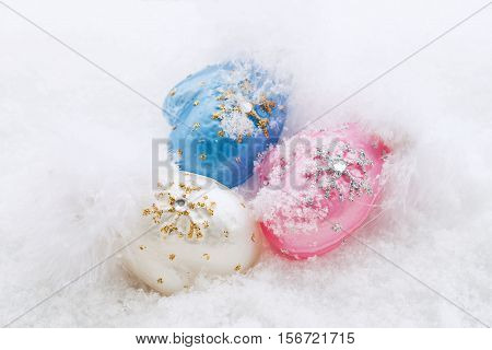 Christmas mittens. Glass Christmas decoration mittens on a background of natural snow. Christmas and New Year.
