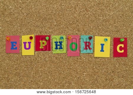 Euphoric word written on colorful sticky notes pinned on cork board.