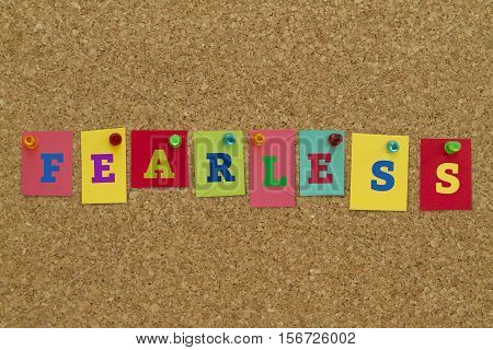 Fearless word written on colorful sticky notes pinned on cork board.