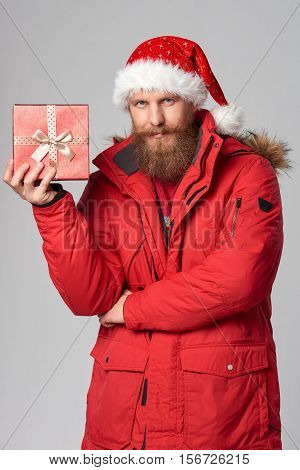 Bearded man in red winter jacket and christmas hat holding small gift box, over grey background