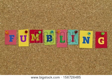 Fumbling word written on colorful sticky notes pinned on cork board.