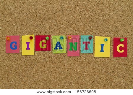 Gigantic word written on colorful sticky notes pinned on cork board.