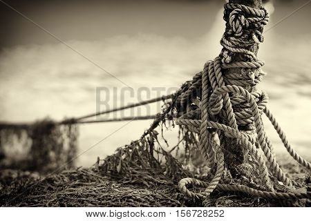 Tied up ship rope on Norway beach in sepia hd