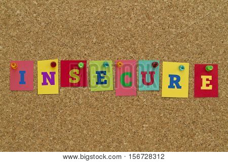 Insecure word written on colorful sticky notes pinned on cork board.