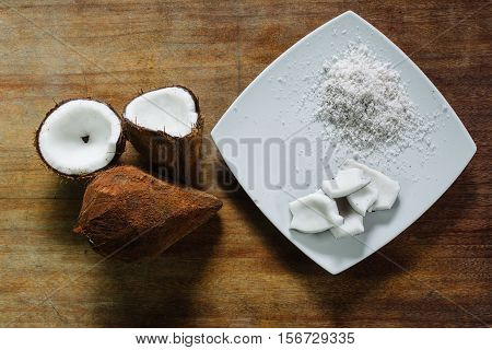 Coconut and coconut grated on a table of wood.