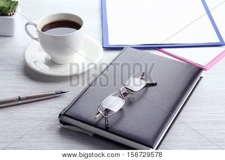 Glasses, notebook and cup of coffee on wooden table. Healthy eyes concept
