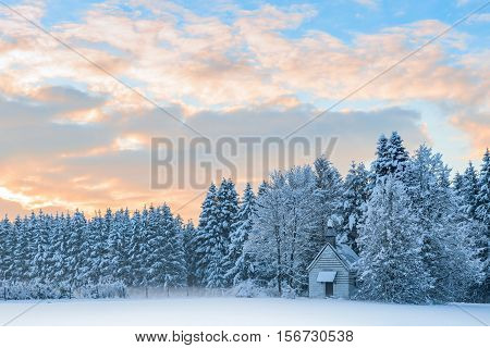 Small wooden chapel in snowbound frosty forest under morning sunrise sky. Amazing idyllic winter landscape in Bavarian rural region Allgaeu.